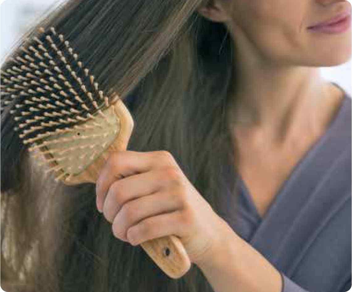 girl brushing through her long thick hair