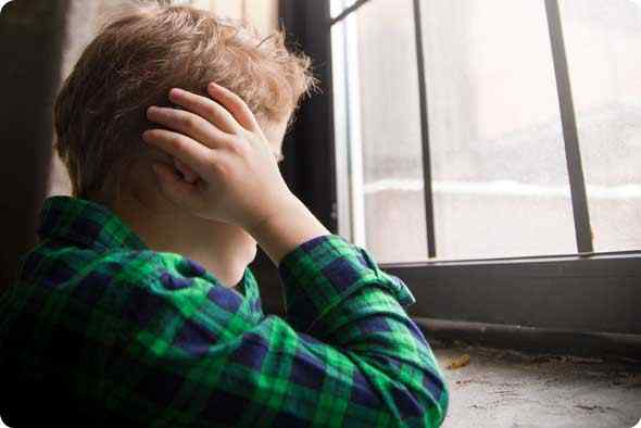 a male autistic child looking across the window covering his ears wth his hands